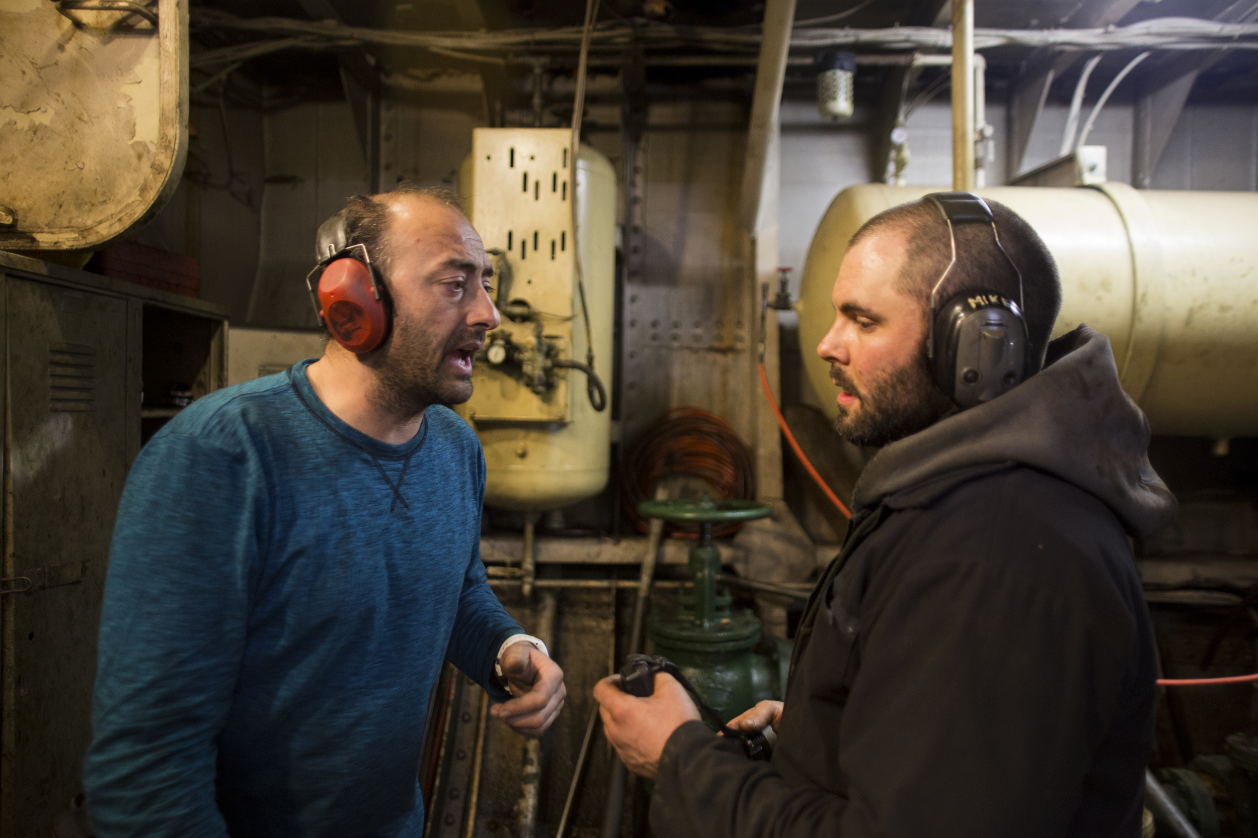 Vinik and his deckhand, Chris, yell over the massive sound of the  Oxman's  main engine while fixing damage in the engine room during a late-night run up the Hudson.