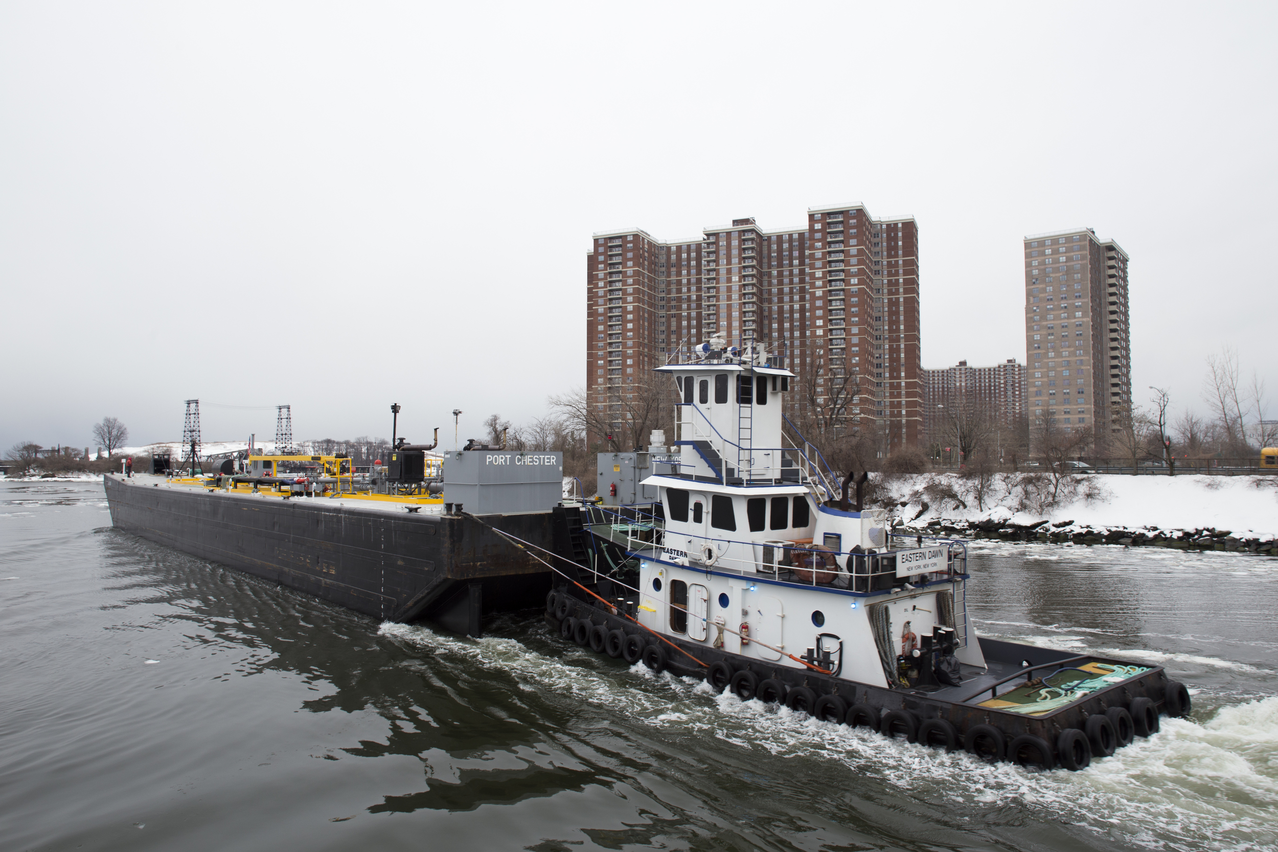 A Vane Brothers tug pushes an empty oil barge past housing projects in the Bronx, which will use the oil for heat. Barges sit high in the water when empty, forcing captains to climb to an upper cockpit, often just a tiny unheated room with a steering wheel, to see over the top of the barge.
