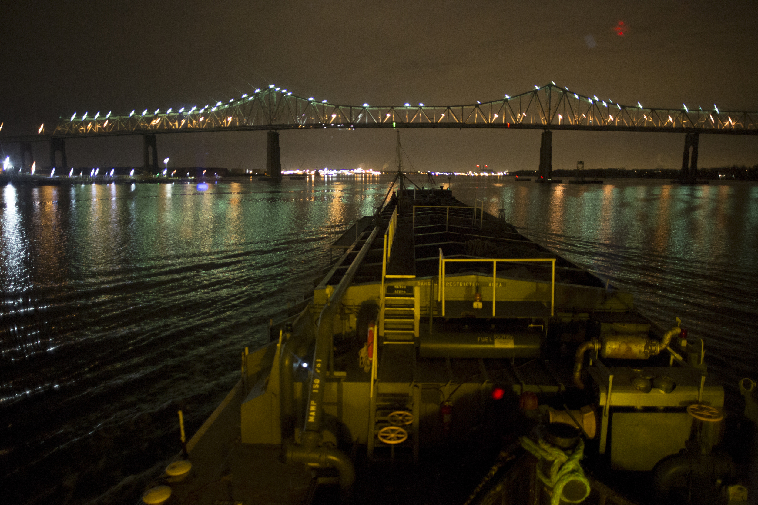 The view from the bridge of a tug pushing a fully-loaded oil barge up the East River on a nighttime run to deliver heating oil to the Bronx.