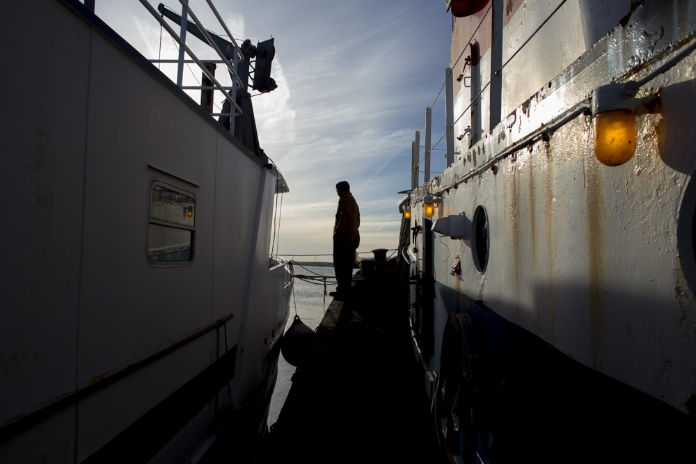 Mike Vinik stands on the edge of his tug, Charles Oxman , preparing to cross to the houseboat he lives on outside of Perth Amboy, New Jersey.