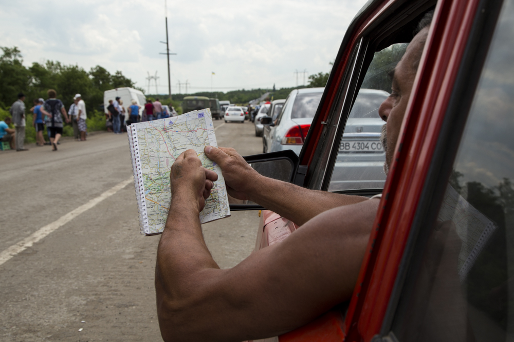 Valentino, a Ukrainian former factory worker who lived in the United States during the 1990s, shows his long route through eastern Ukraine and rebel-held territory to get home at a checkpoint outside Artiemvisk. 2015