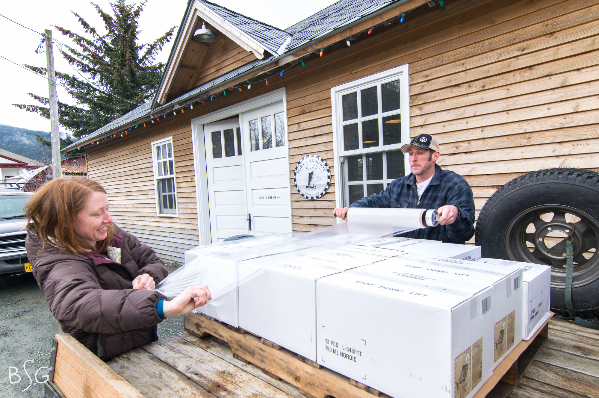 Shade and Copeland package a batch of 50 Fathoms Gin for shipment to Juneau in front of the distillery. The couple renovated the building using local wood and a local workforce.