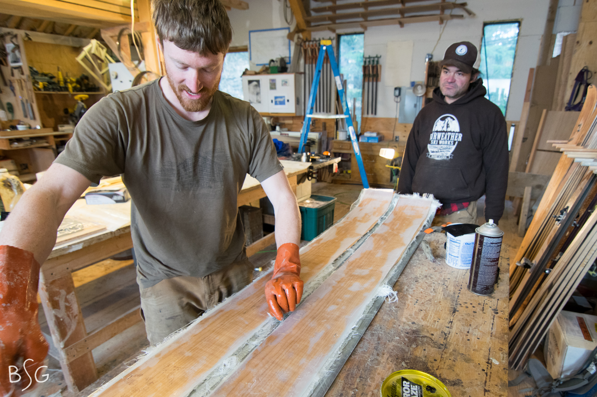 Kraft and Seward add a top sheet before loading the skis into their homemade wooden ski press that will add 180 degrees of heat and up to 60,000 lbs of pressure.