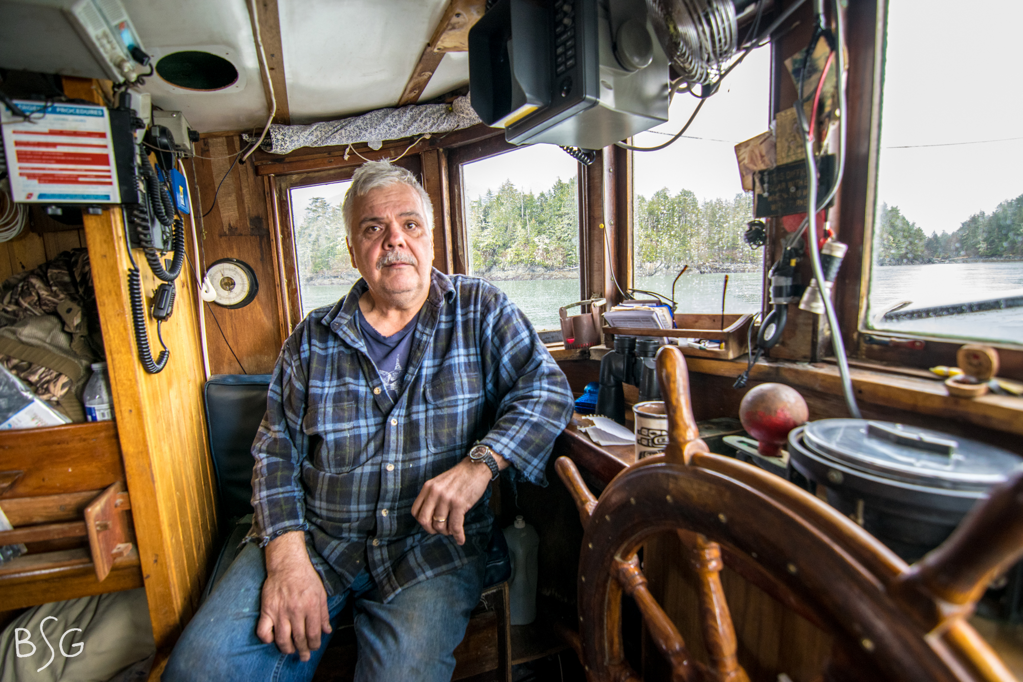 Vernon Hill sits in the wooden wheelhouse of the Shirley N. He and his crew spent nine days in Sitka Sound in April collecting herring eggs on branches to bring back to the community of Hoonah. Sitka Sound is the final remaining stronghold of herring in the region.