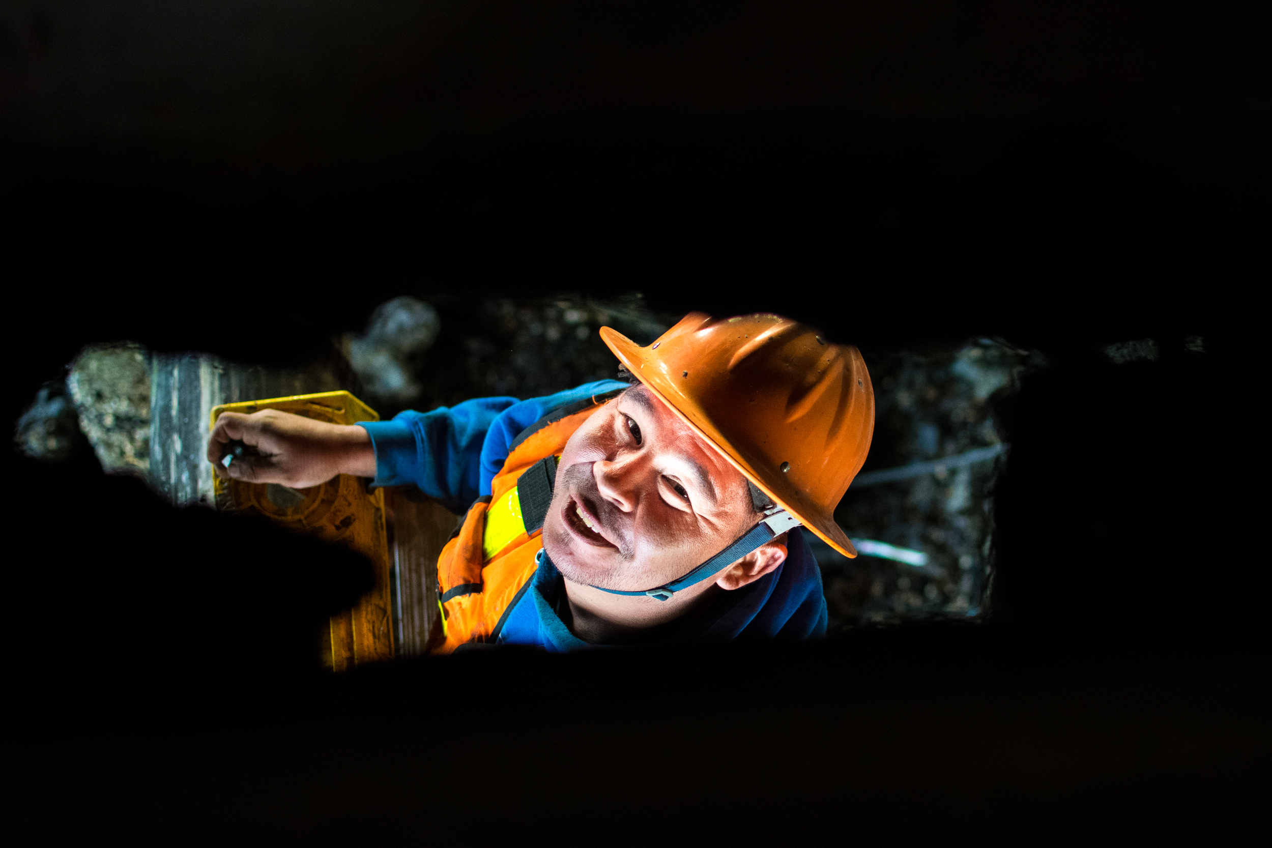 Spotted through a hole in the cannery's floorboards, Kake local, Tyrone Paul grins while stabilizing a wood piling.