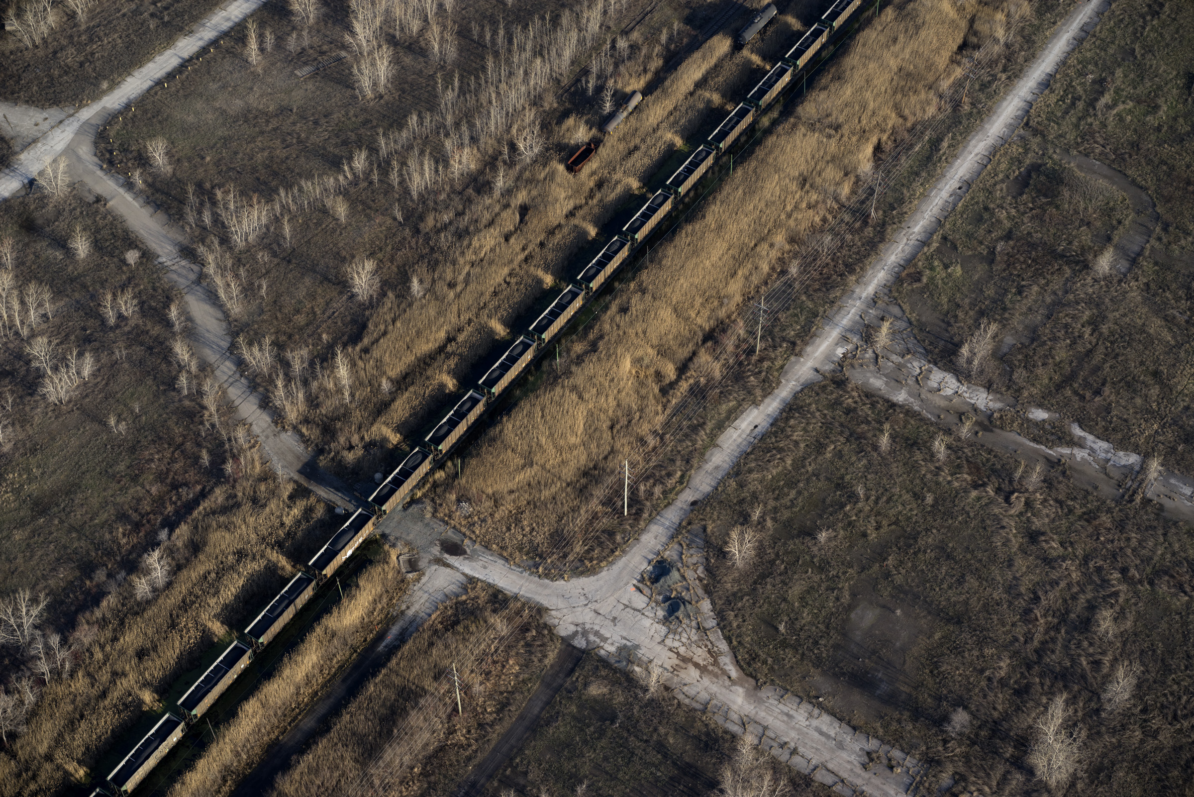 Petcoke filled train moving through a brownfield, former steel mill site, 2014. Terry Evans