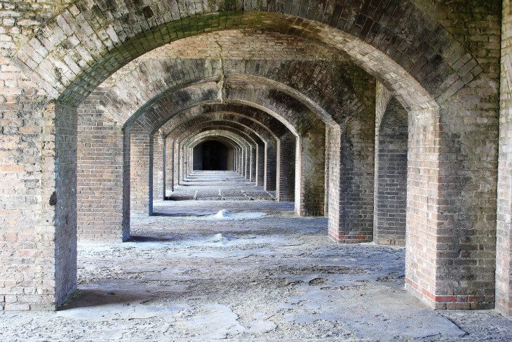 AN INNER CORRIDOR OF FORT JEFFERSON. TO THE LEFT IS THE OUTER COURTYARD.  TO THE RIGHT ARE FORTIFIED GUN EMPLACEMENTS.  STRAIGHT AHEAD IS OUR ENTERTAINMENT CENTER AND DIRECTLY BEHIND US IS THE SHUFFLEBOARD COURT.