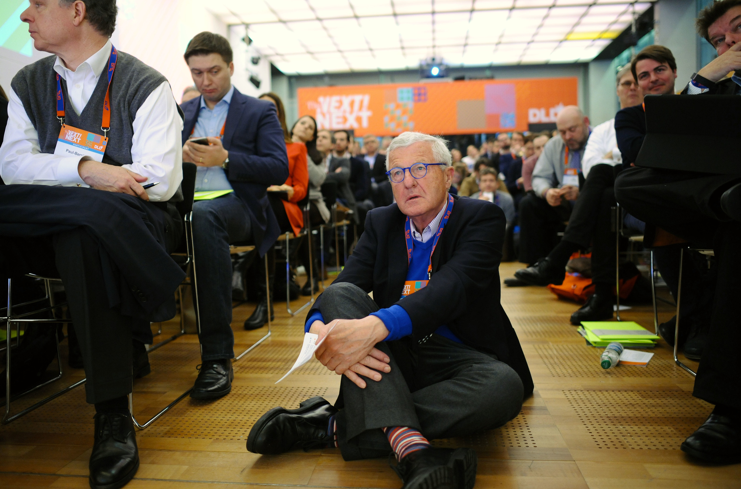 Publisher Dirk Ippen sits on the floor and listens to a speaker. © Andreas Gebert/Picture Alliance/Hubert Burda Media