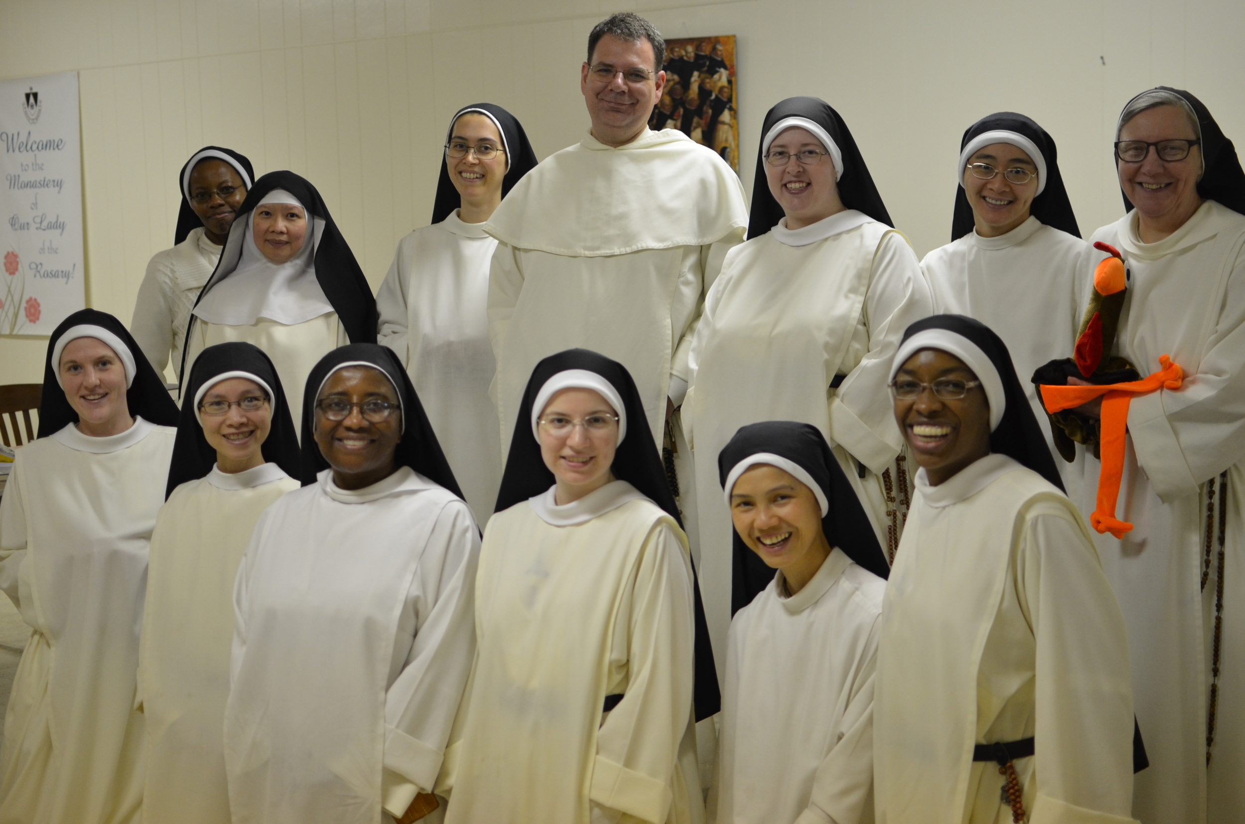 "Class photo with Fr. Andrew Hofer, OP who taught last week's course: ""Introduction to St. Thomas Aquinas"" Back row (L-R): Sr. Fransica (Nairobi, Kenya), Sr. Mary Isabel (Menlo Park, CA), Sr. Dominic Marie (Farmington Hills, MI), Fr. Andrew Hofer, Sr. Mary Cecilia (Summit), Sr. Mary Austin (Los Angelos, CA), Sr. Clara Marie with the class's mascot (Farmington  Hills, MI) Front row (L-R): Sr. Mary Magdalene (Summit), Sr. Marie Therese (Farmington Hills, MI), Sr. Maria of Jesus (Farmington Hills, MI), Sr. Mary Veronica (Summit), Sr. Mary of the Angels (Los Angelos, CA), and Sr. Mary Jacinta (Summit)."
