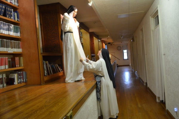 """Sr. Mary Catharine measures Sr. Mary Jacinta's habit on the """"ramp"""" in the dormitory.Below this level is the side aisle of the outside chapel of the monastery."""