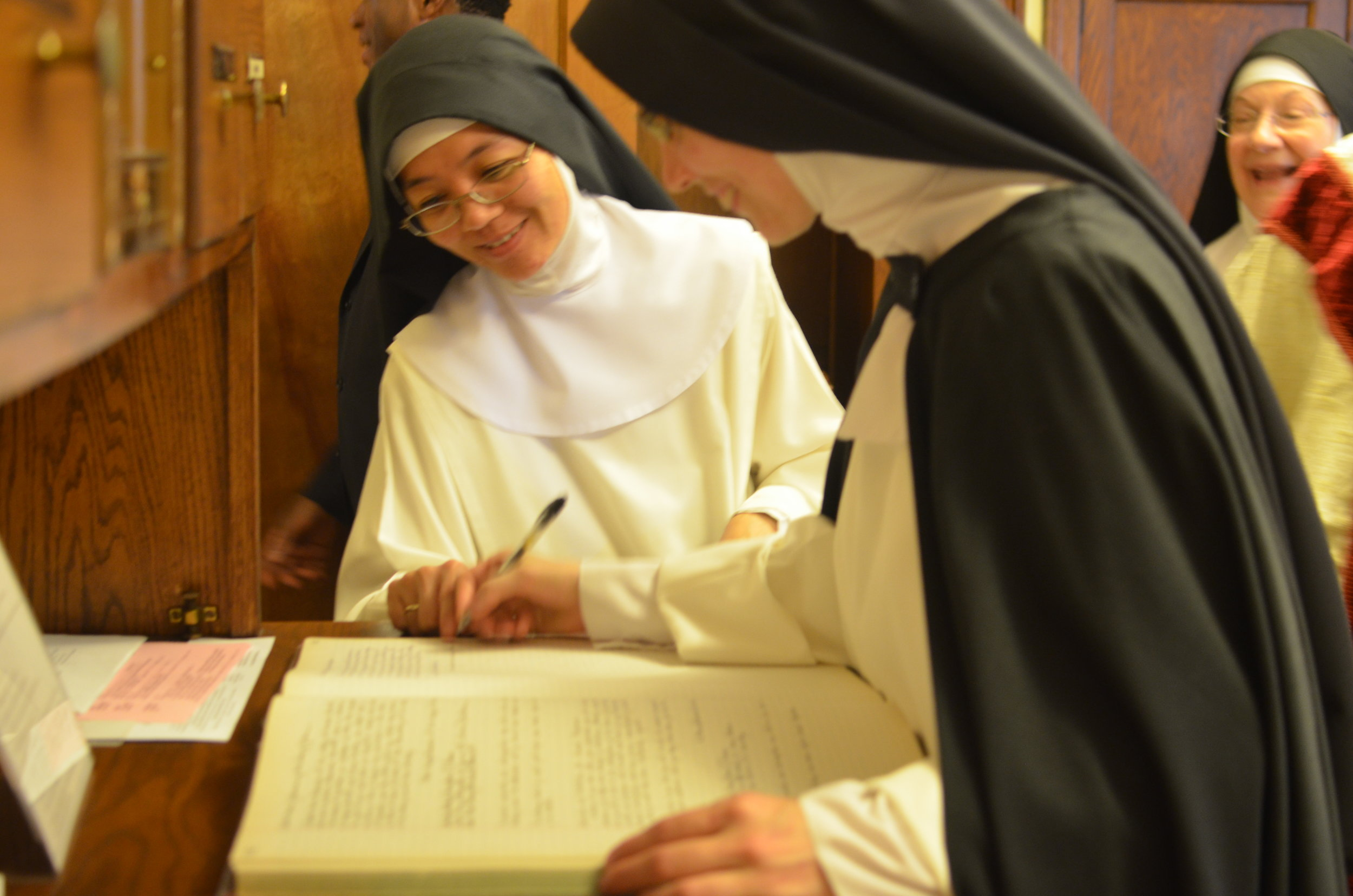 Sister signs her profession in the sacristy after Mass