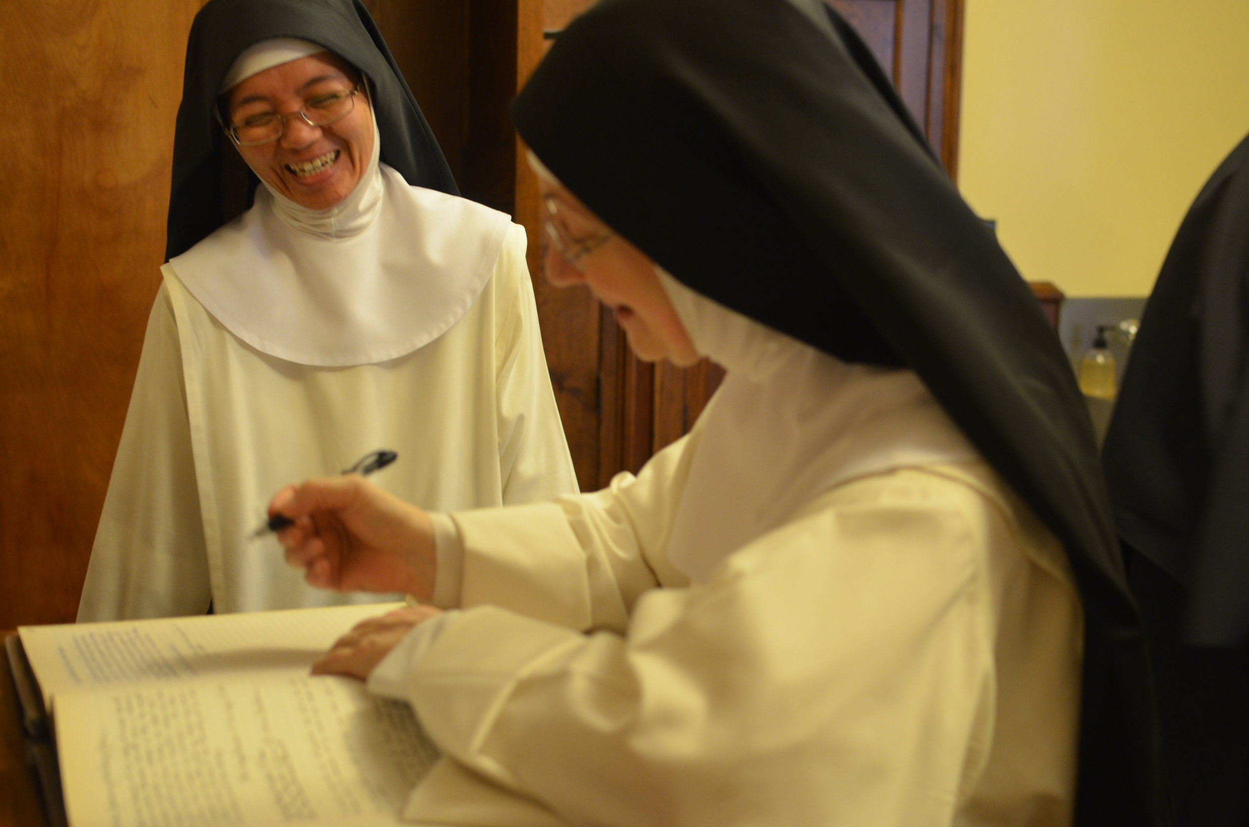 Sr. Denise Marie signs, witnessing to Sister's profession