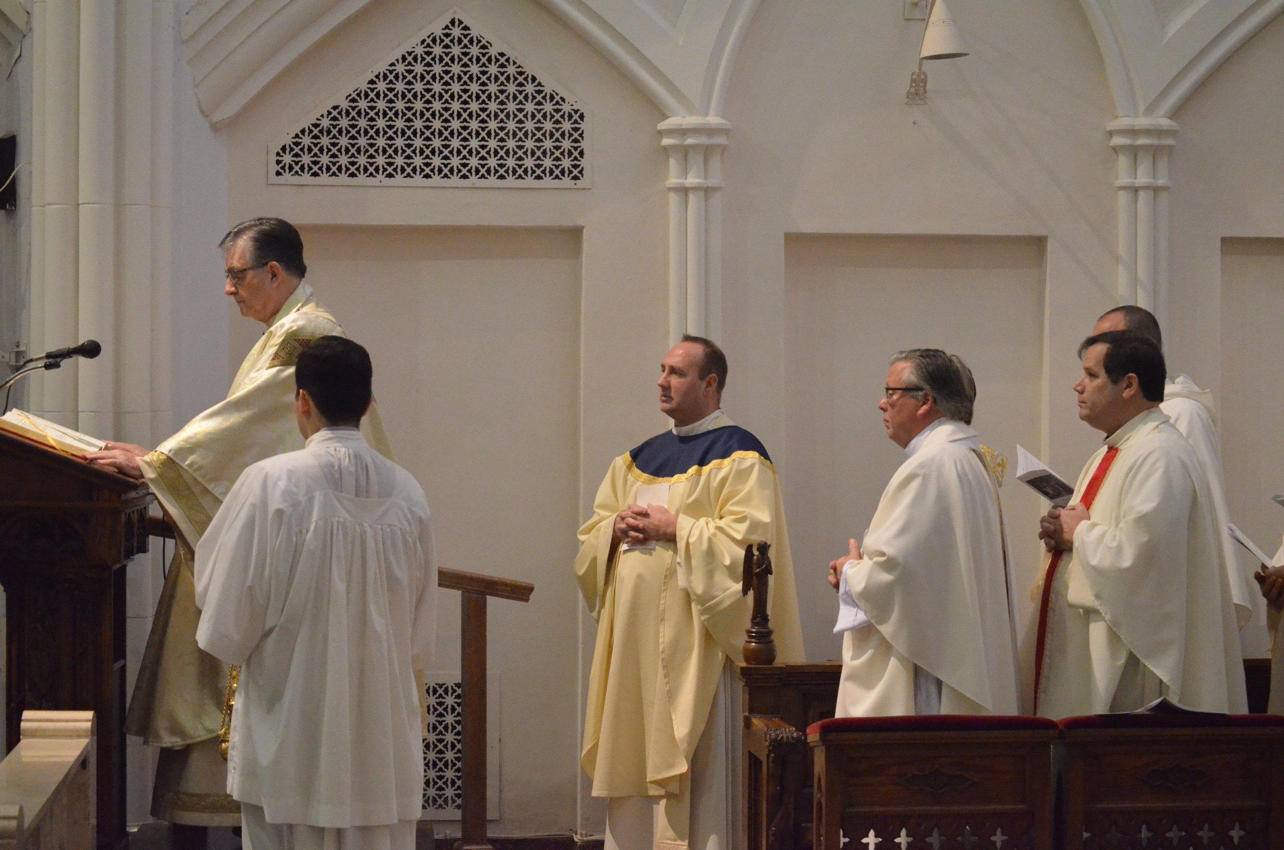 Fr. Gregory Salomone chants the Gospel