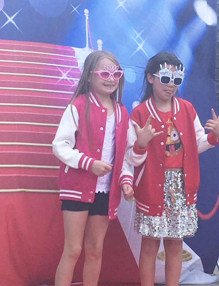 Two girls wearing their custom jackets made at Luvlybubbly