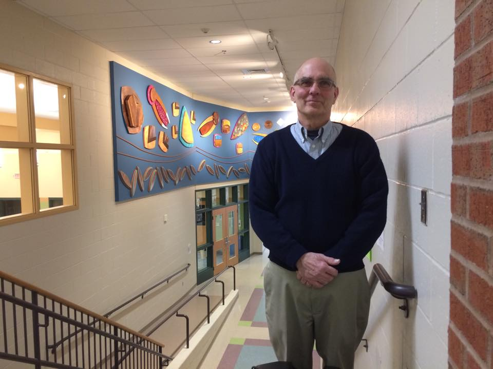 """Michael Kraatz of Canaan in front of """"Diverse Unity"""", a multi-media mural he designed and created in collaboration with his wife, Susan Russell. Thanks to the support from the Brundage Foundation, the Mascoma Bank Foundation, Friends of Mascoma Foundation donors and volunteers, Chris Morse with Experiencing the Arts and Mascoma students in Dave Shinnlinger's wood shop classes. There are pieces of wood in the mural from the old gymnasium, bleachers and library shelves, along with pieces students created. Please go view this in the entrance hall to the media center."""