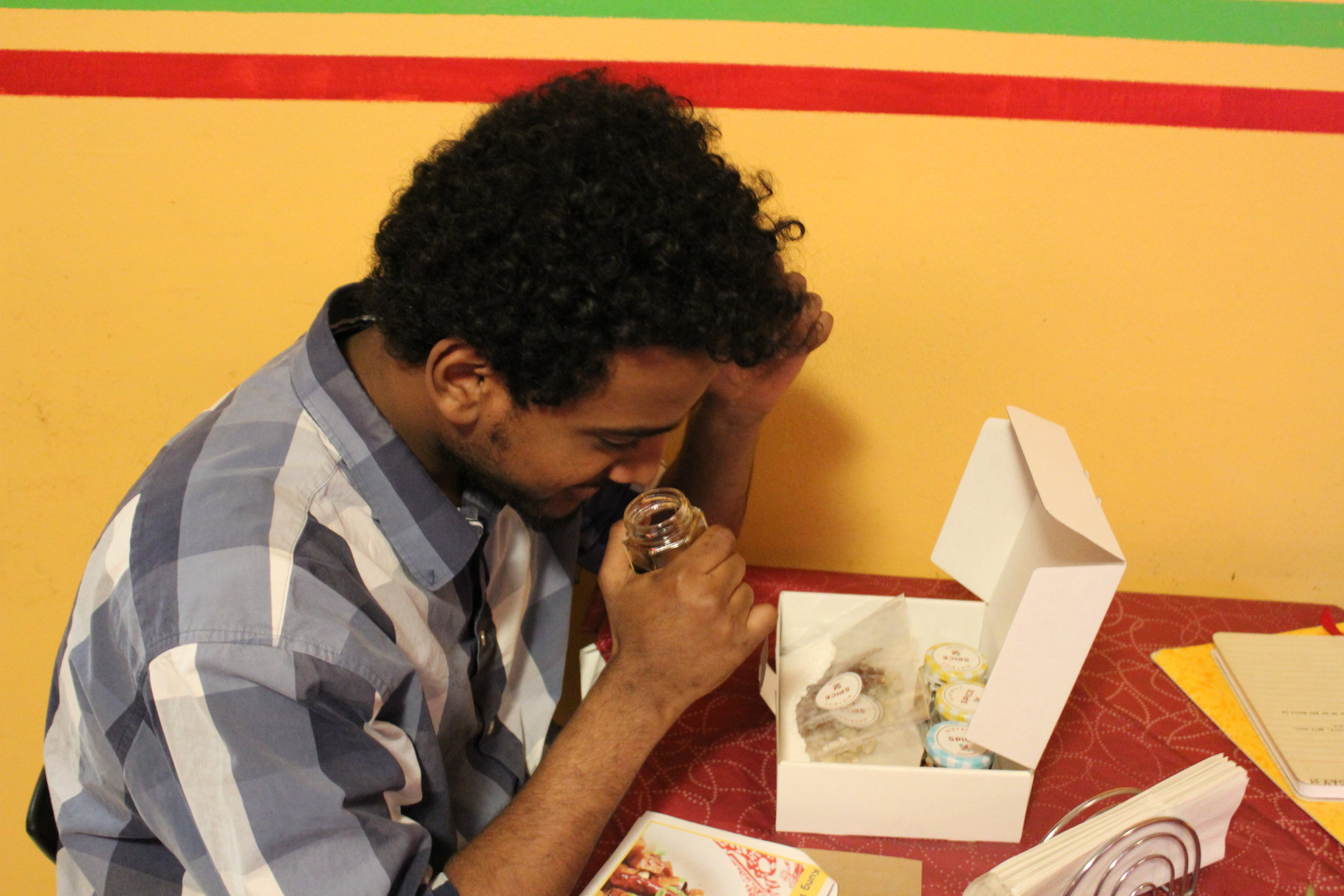Jonas, an Eritrean employee at Ma'ed, smelling the ingredients from the Kong Pao flavor kit
