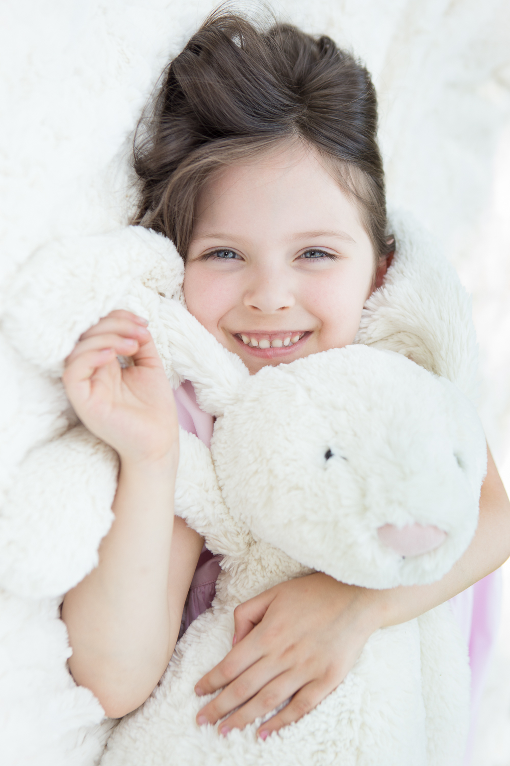 portrait of a little girl with her stuffed rabbit