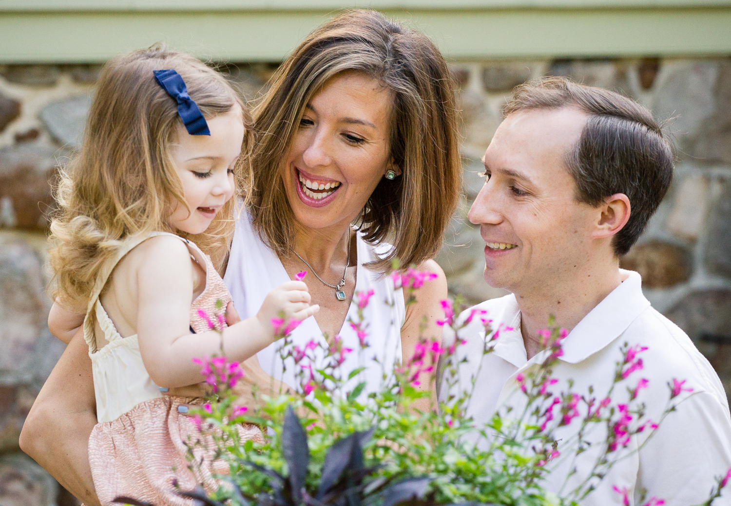 Photography by Aliza at Appleford Estate of parents with their little girl exploring the flowers
