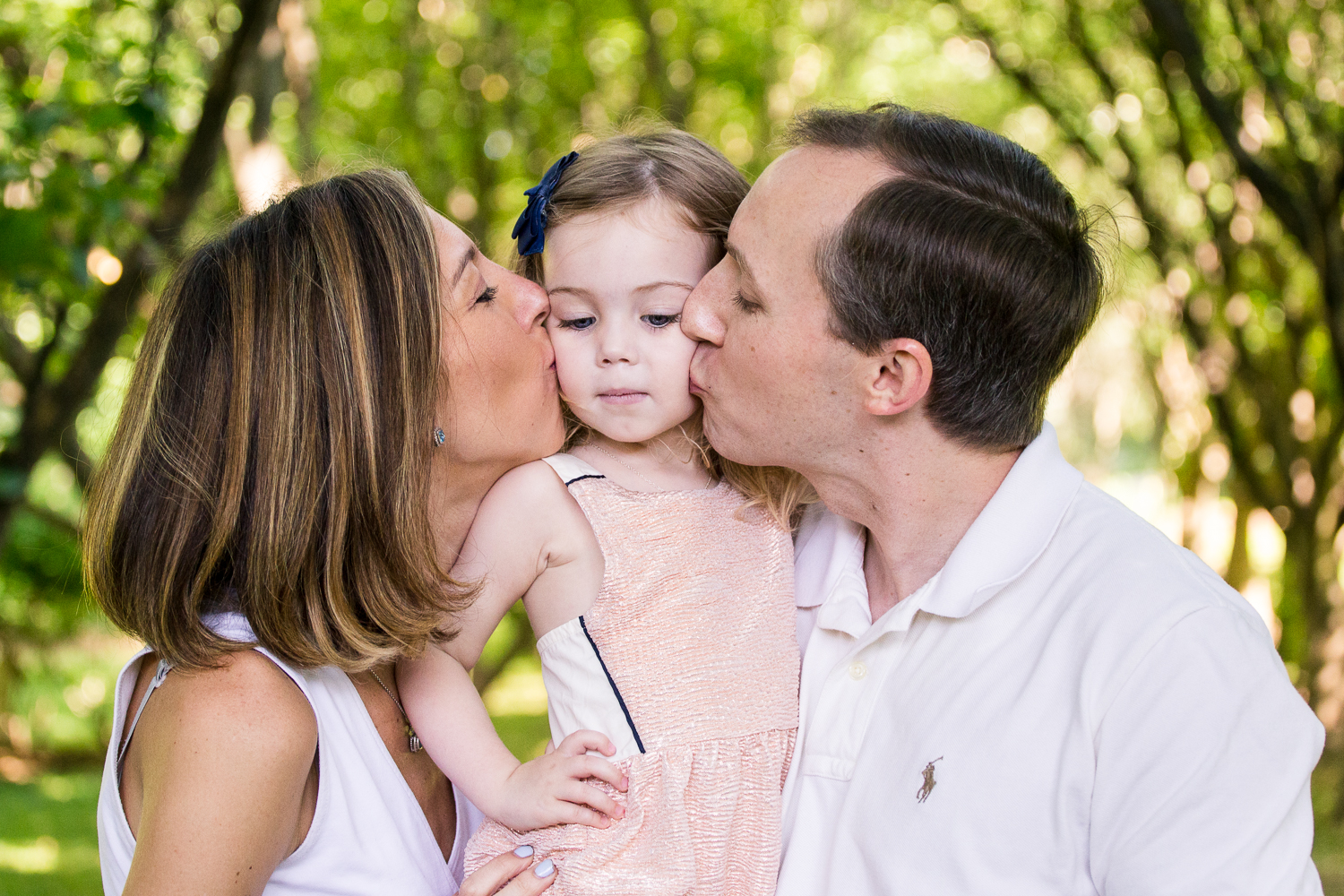 Portrait with attitude of mom and dad kissing their little girls cheeks at Appleford Estate