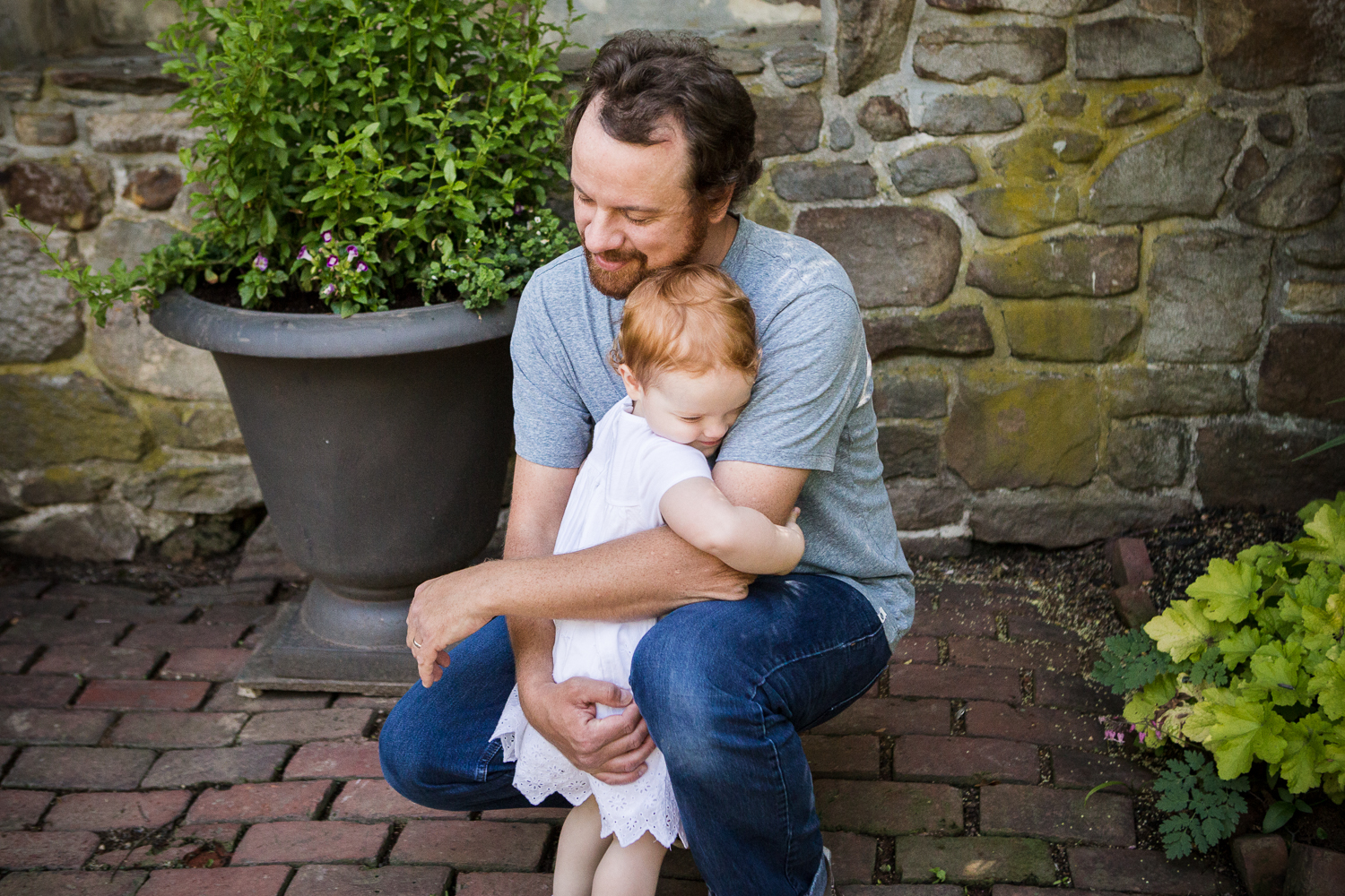 Photo of a toddler redhead girl hugging her squatting father at Appleford Estate in Villanova