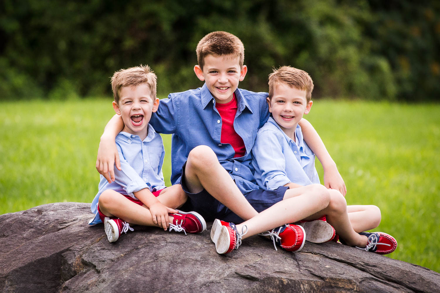 Portrait of 3 brothers sitting on a big rock