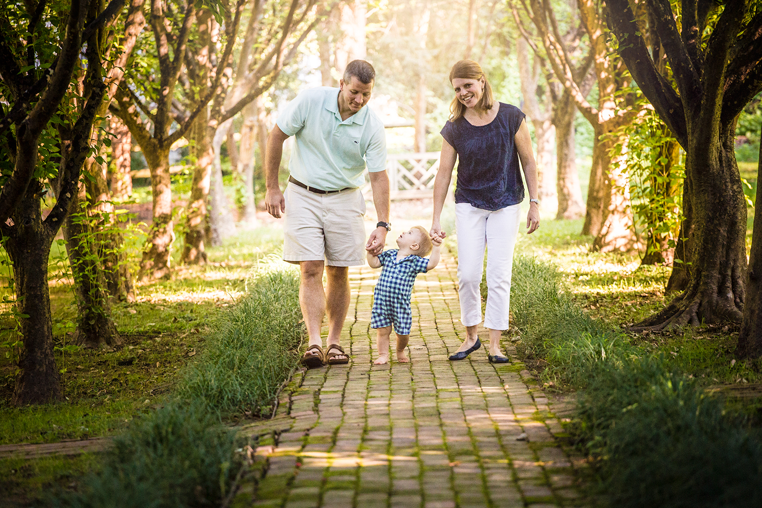 Photo of parents holding their little boys' hands walking through a path at Appleford Estate