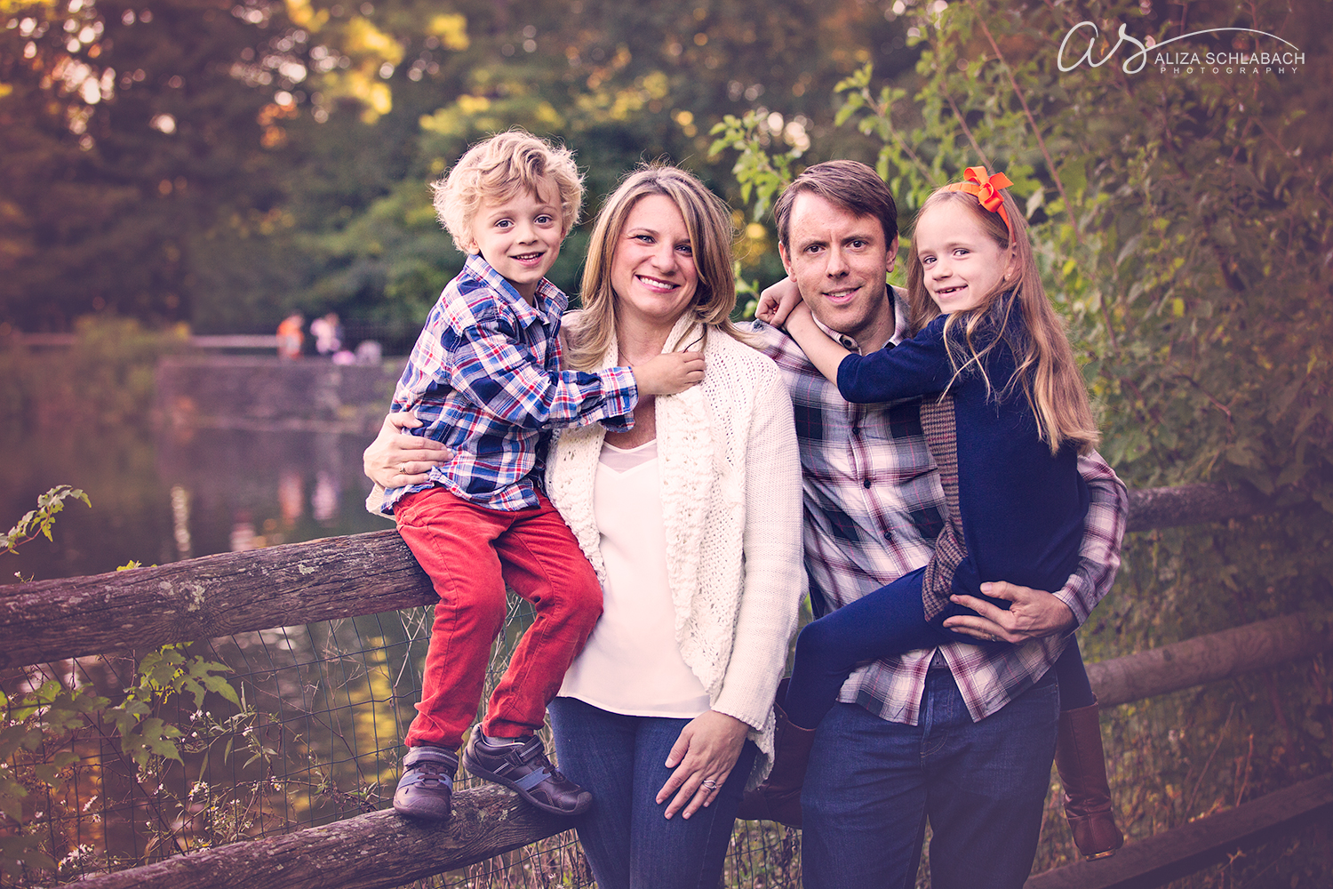 Photo of a family of 4 on the fence near a duck pond