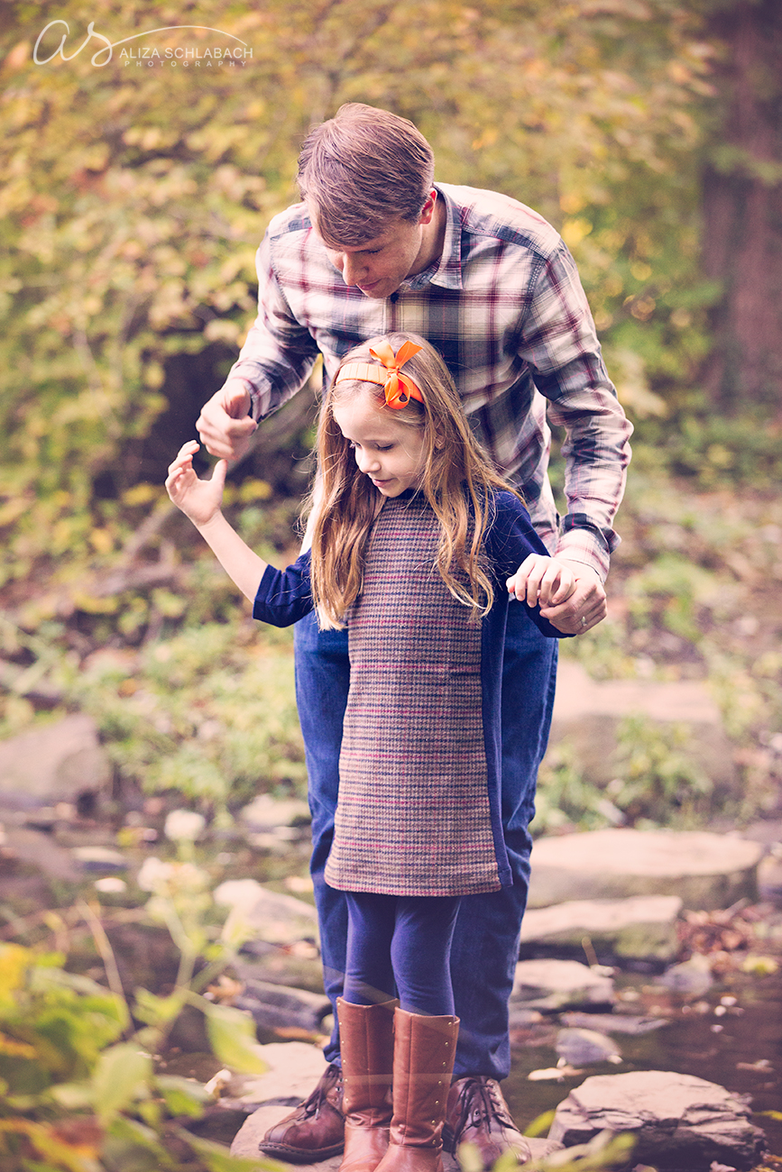 Fall photo of a dad holding his daughters hands as he helps her across some rocks to cross a stream