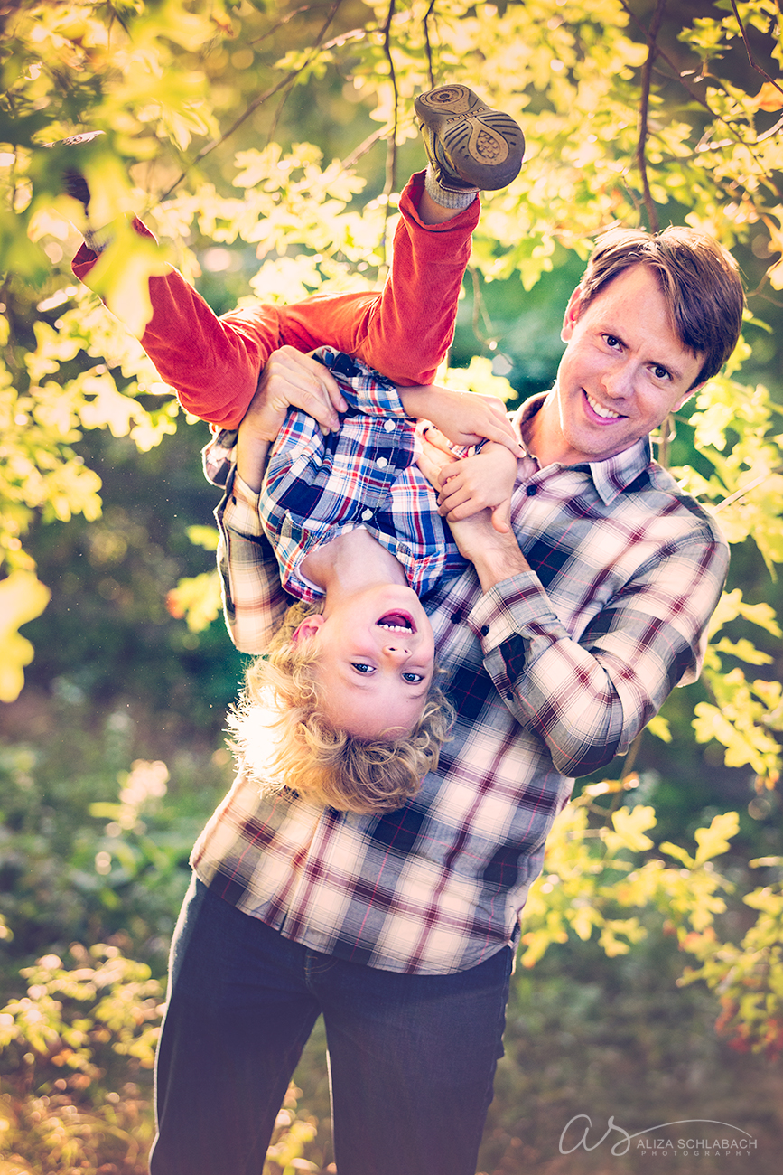 Fall photo of a dad holding his little boy upside down and laughing