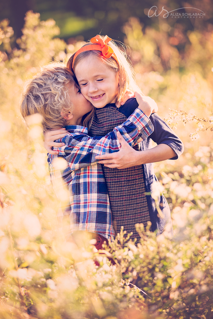 Golden hour portrait of a little boy and his sister hugging each other in a field at Haverford College