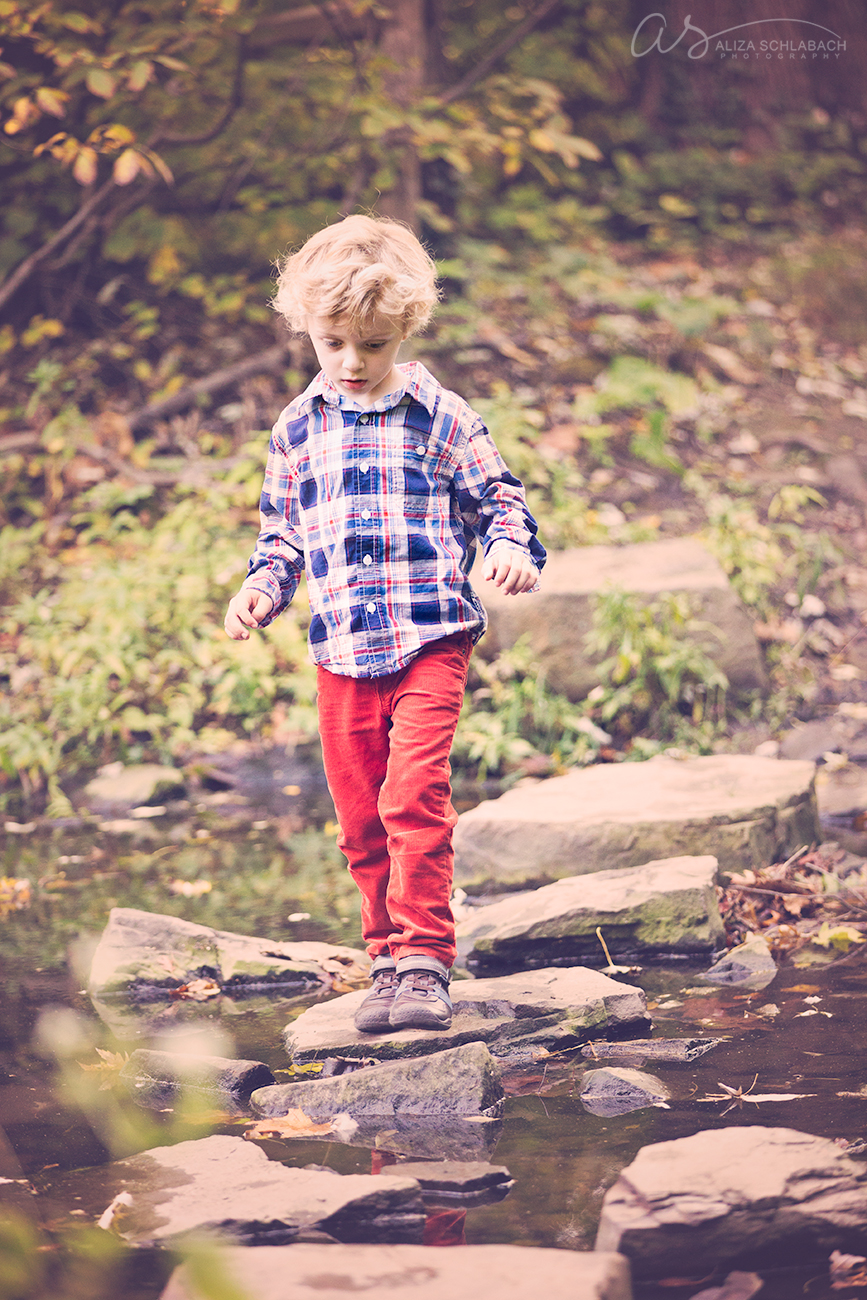 Photo of a little boy crossing the rocks at the pond