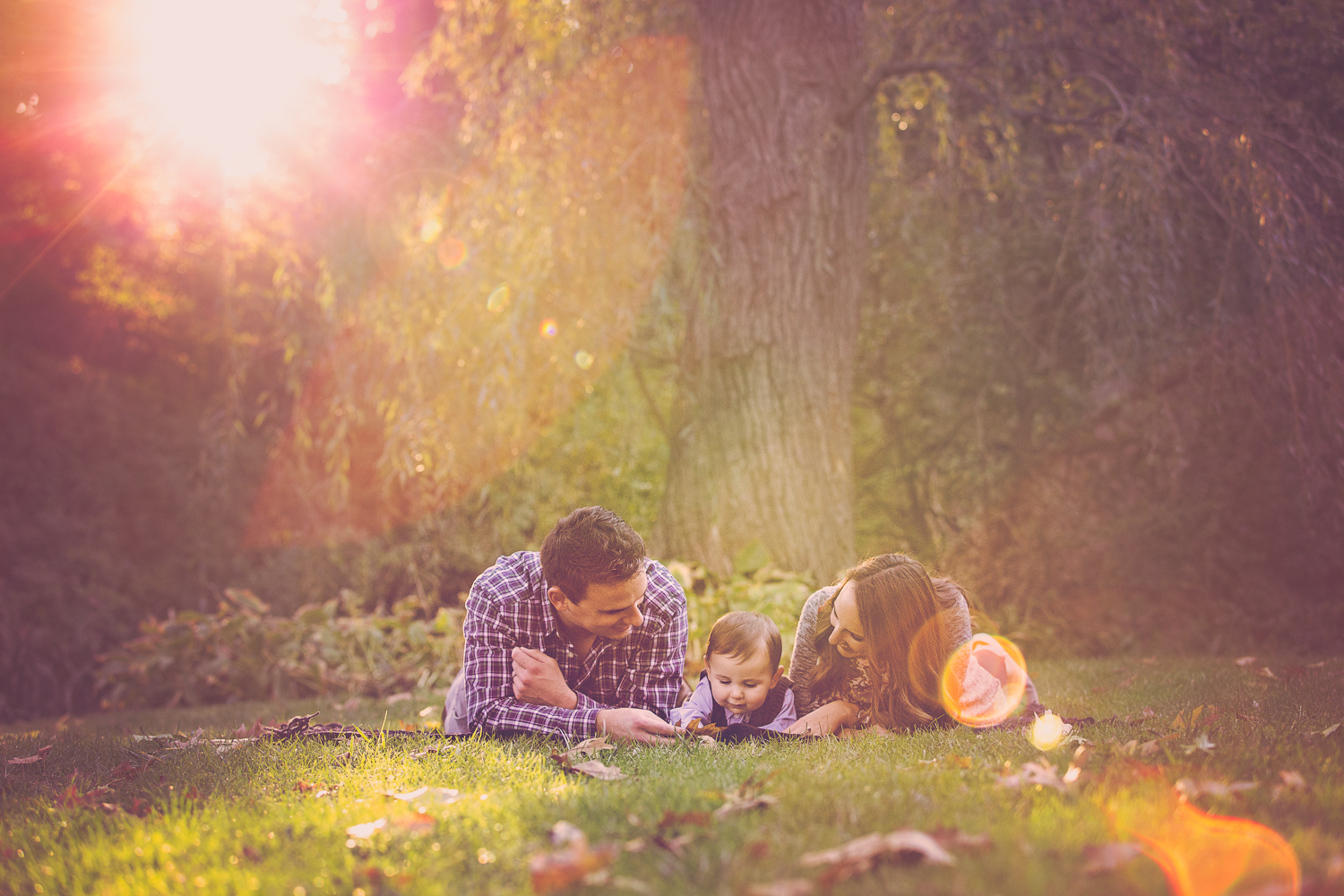 Fall portrait with great sun flare of parents with their son lying on a blanket