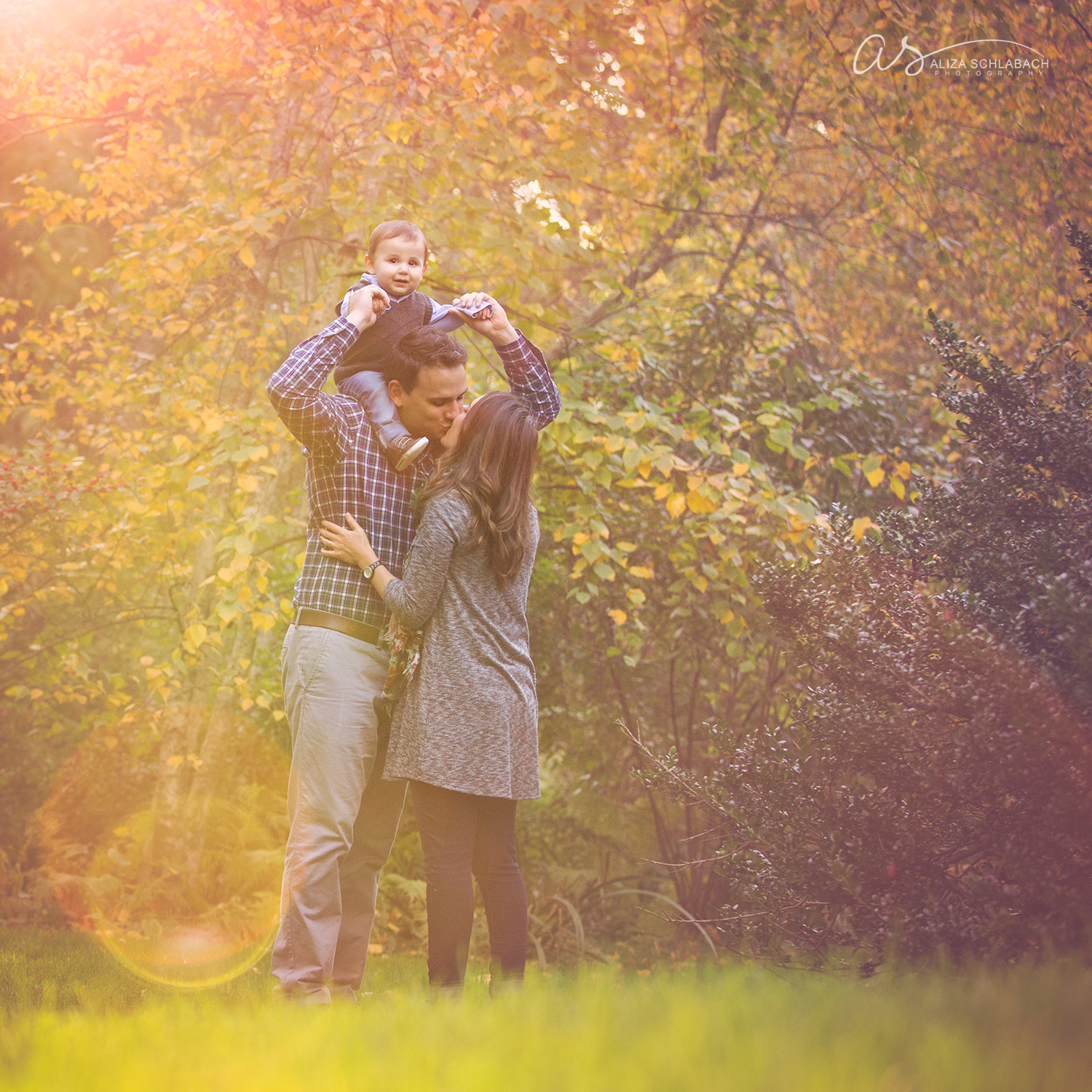 Golden hour fall portrait of a couple kissing with their little boy on daddy's shoulders