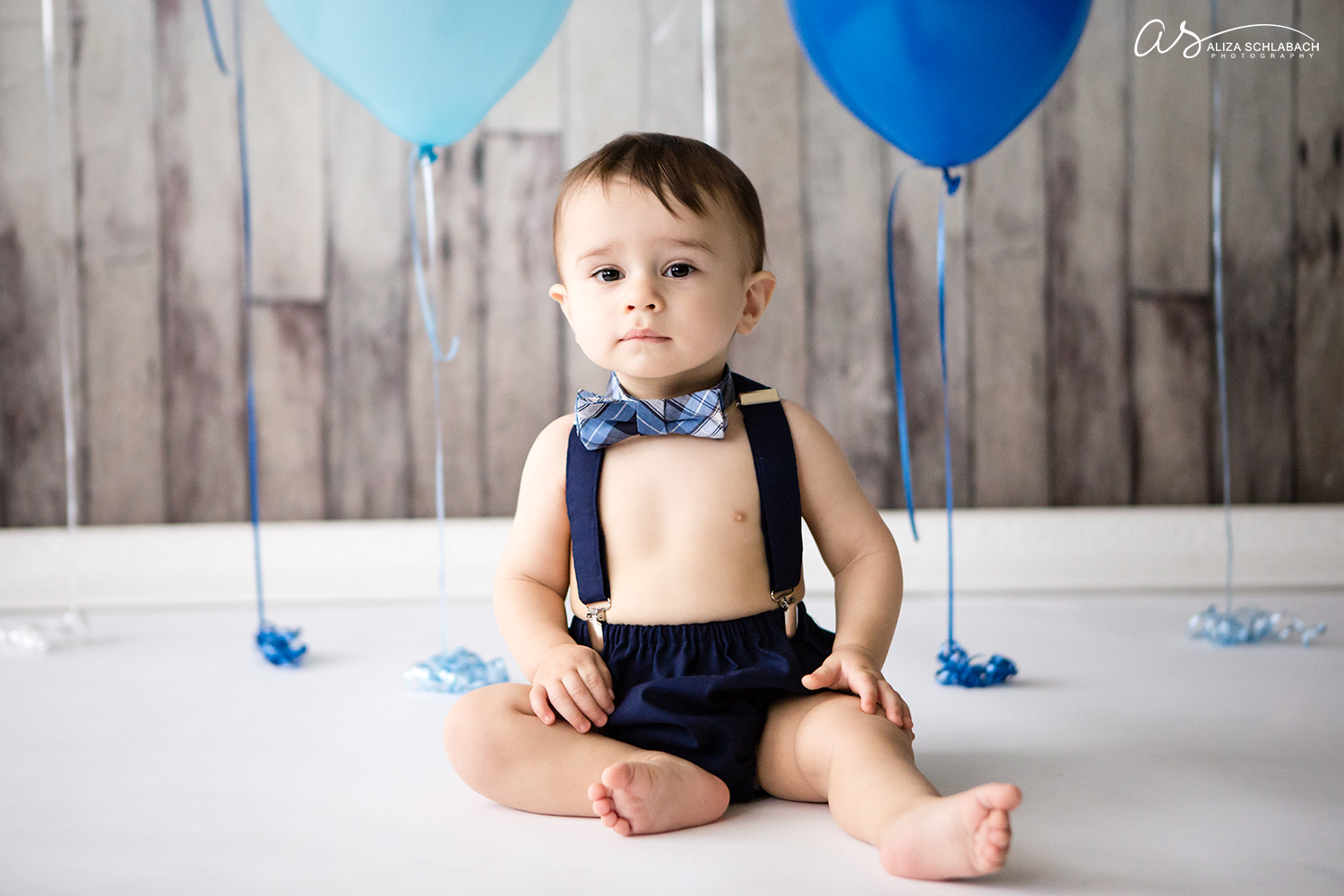 Photo of a baby in a bowtie during his cake smash photography session
