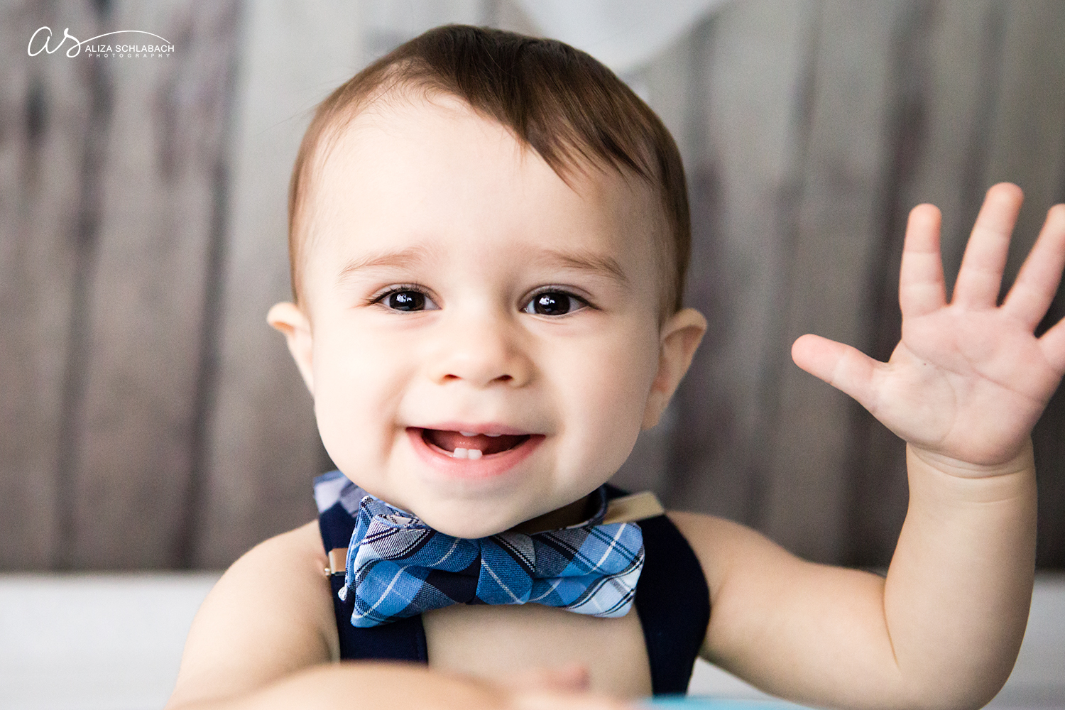 Baby with a bowtie waving at the camera