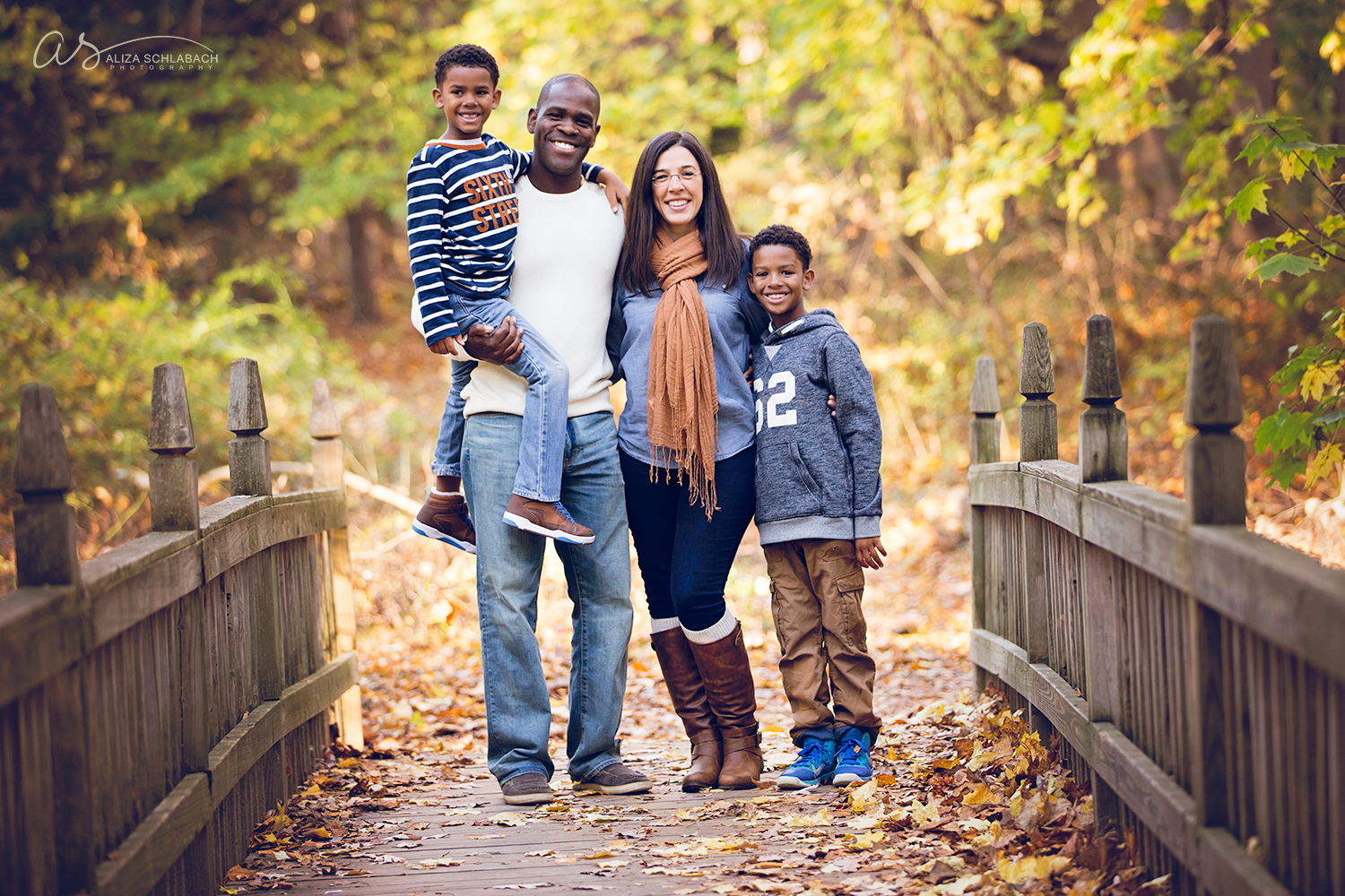 Fall portrait at golden hour on a bridge of a mixed race family