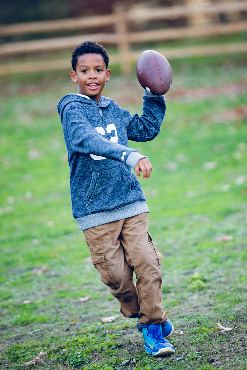 Photo of a little boy throwing a football