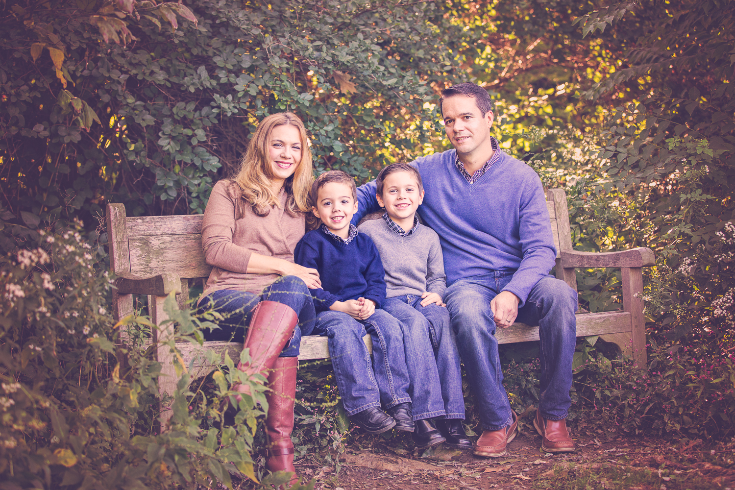 Family photo on a park bench with blue and camel color scheme