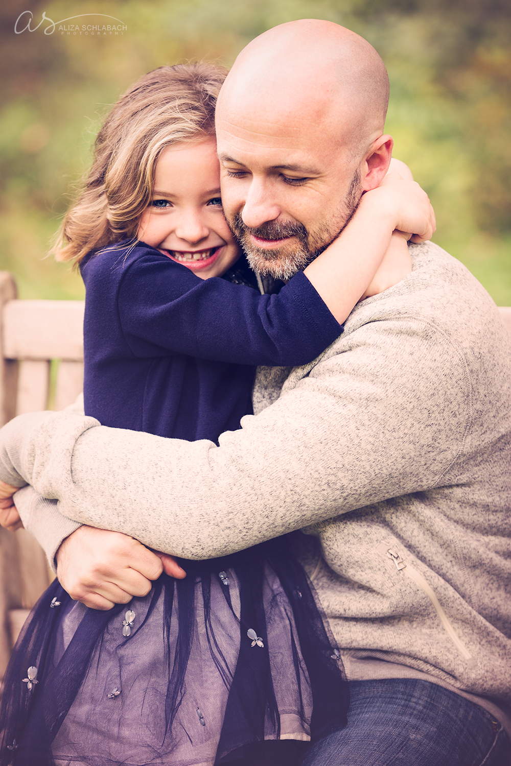 Photo of a cute girl smiling and hugging her bald father