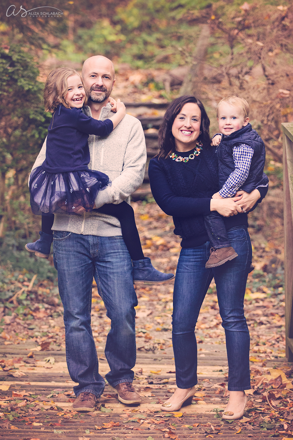 Fall photograph of a mom and dad and 2 kids with blues and creams color scheme