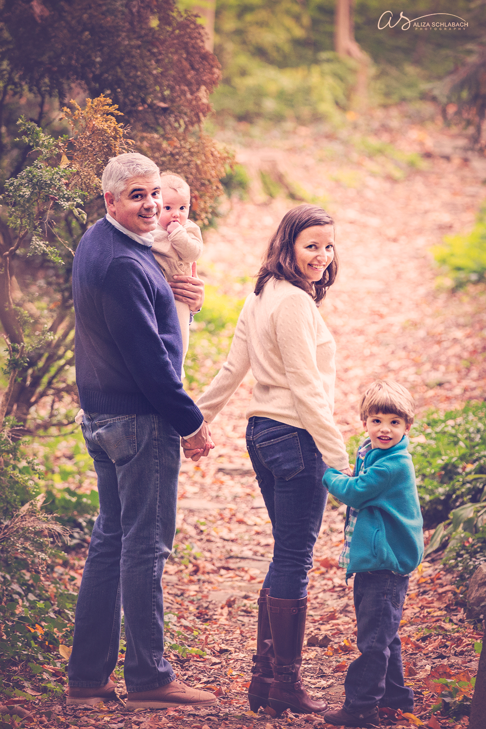 Fall family photo of mom and dad with baby and little boy, turning back to look at camera