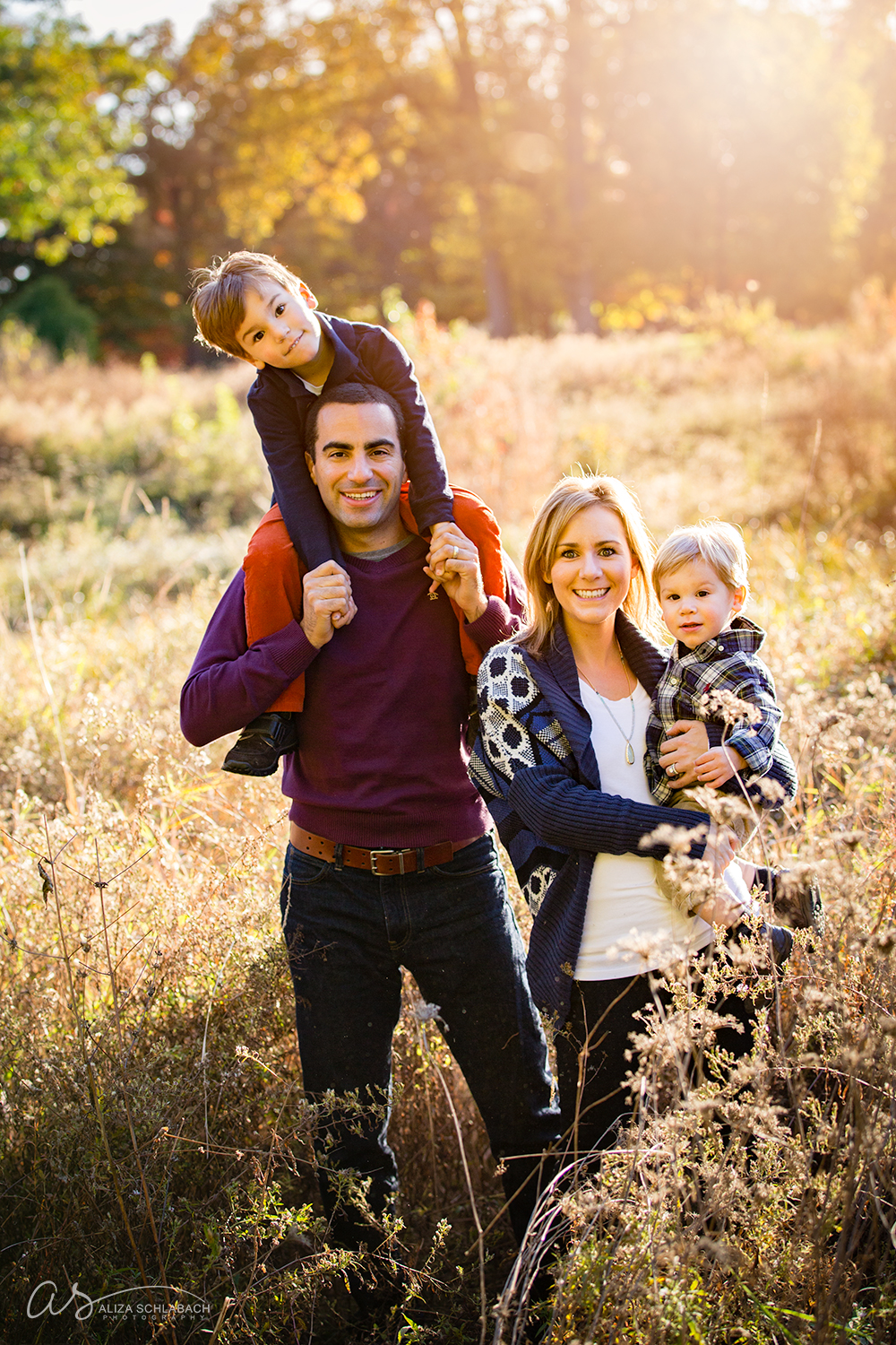 Family fall photo with boy on dad's shoulder's in the field at sunset