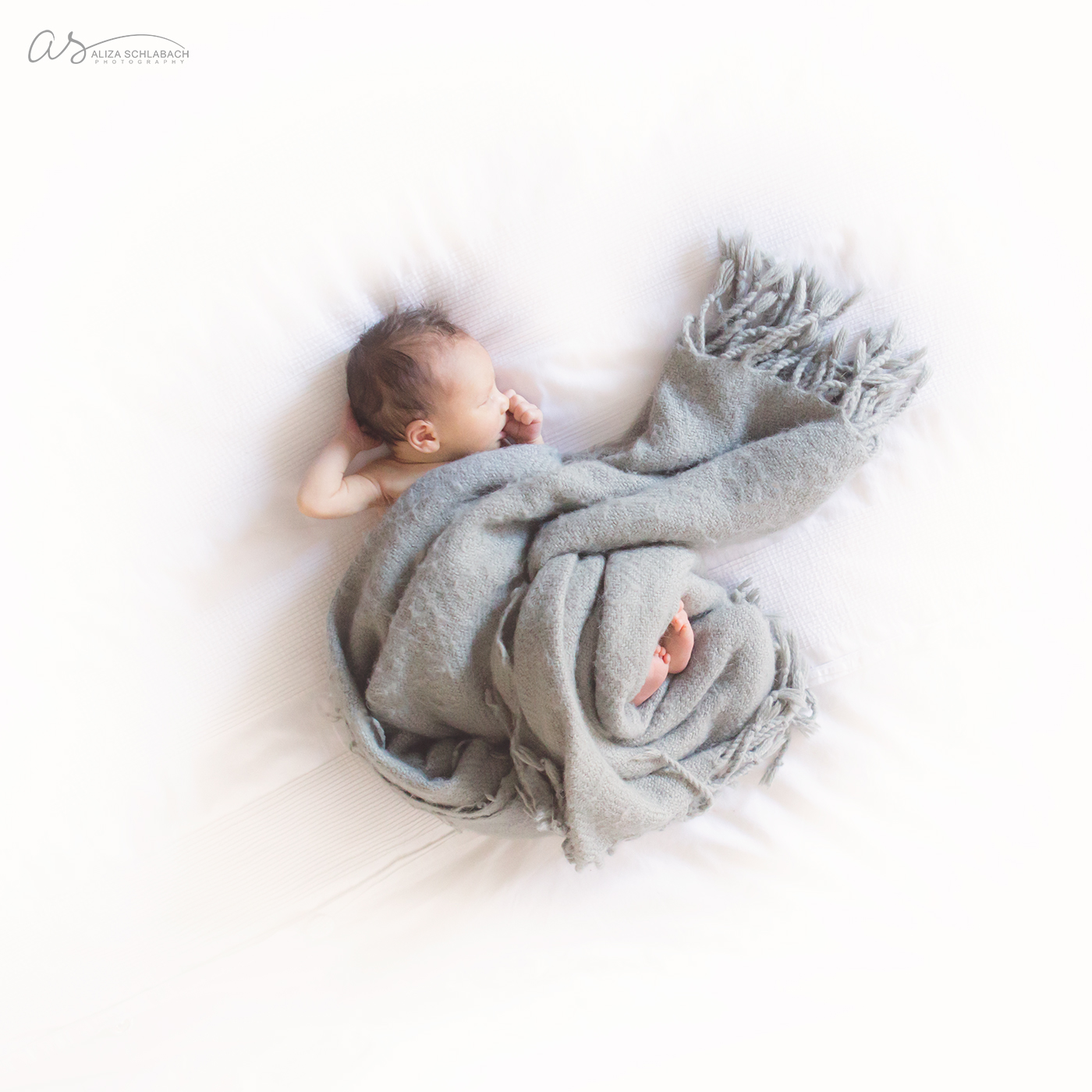 Newborn baby sucking thumb, curled up in a blanked on a white bed