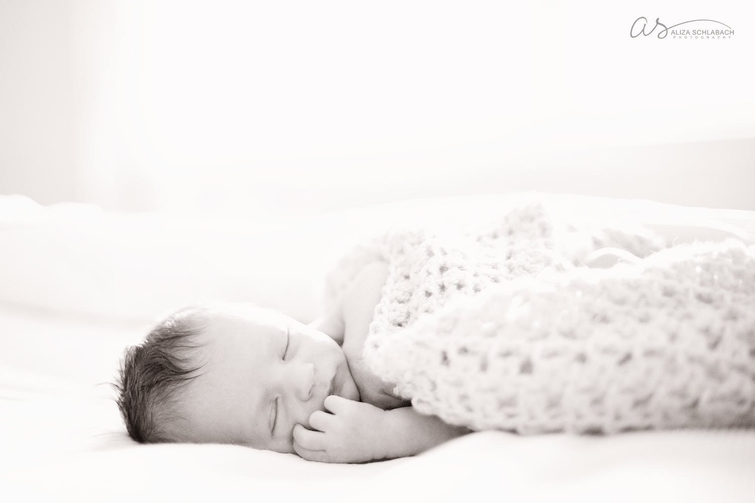 black and white photo of a newborn baby on a white bed, white background, soft crocheted blanket