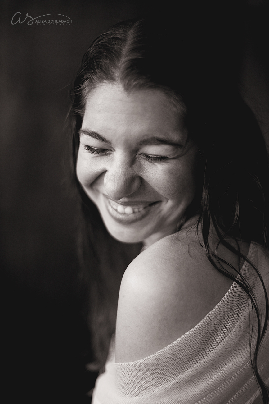 Black and white portrait of a young woman laughing