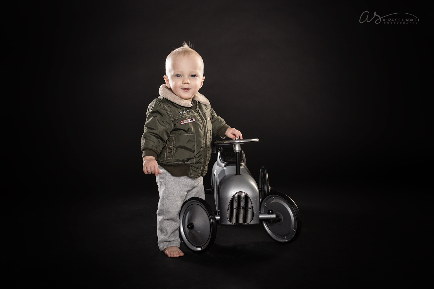 Portrait of a 1 year old baby in a bomber jacket next to a retro push car toy