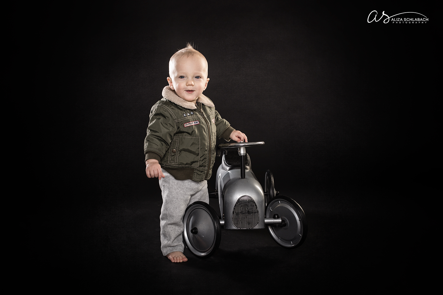 Photo of one year old boy with vintage ride on car and bomber jacket
