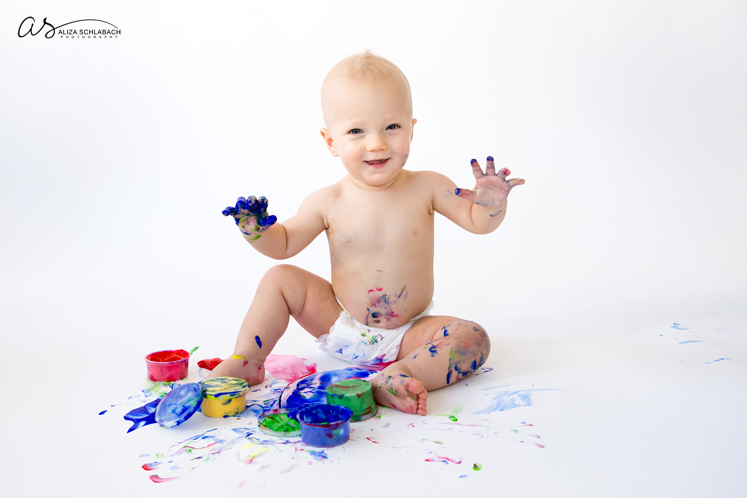 Photo of smiling one year old boy holding up his fingerpaint covered hands