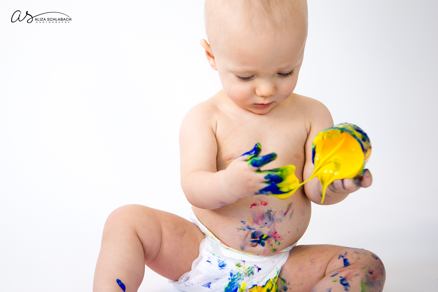 Photo of one year old naked baby boy about to spill fingerpaint