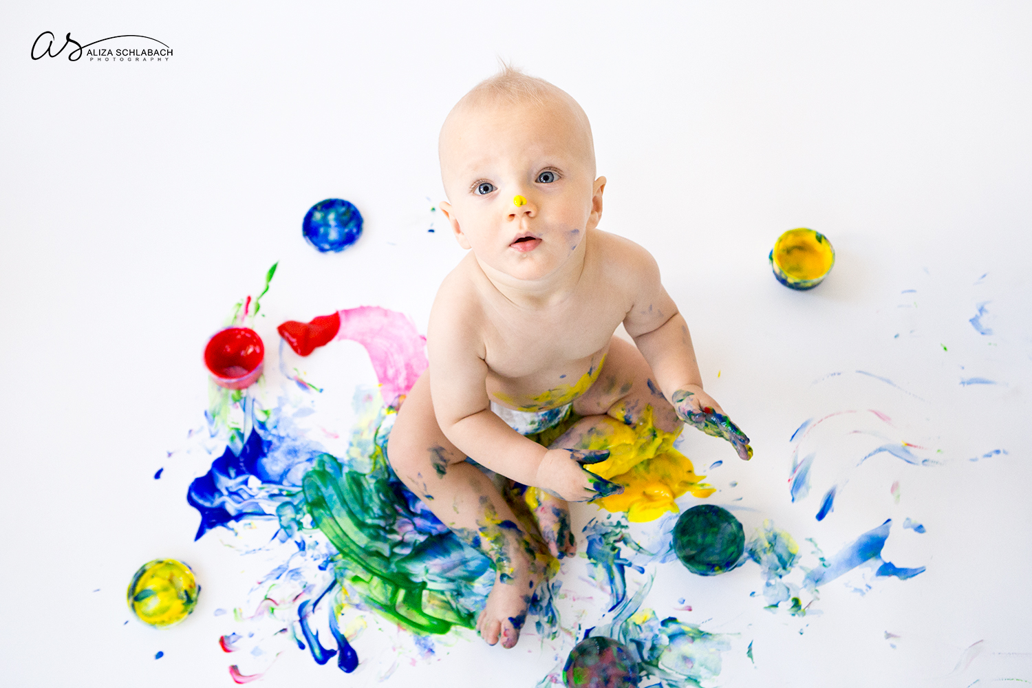 Photo of fingerpainting naked one year old boy looking up at camera
